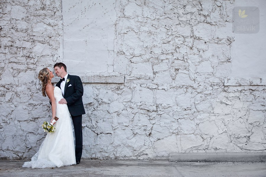 Bride and groom by a gray wall